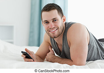 Happy man using his mobile phone in his bedroom