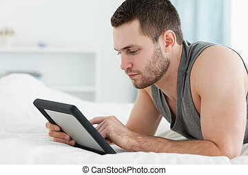 Handsome man using a tablet computer while lying on his...