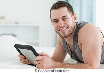 Happy man using a tablet computer while lying on his belly