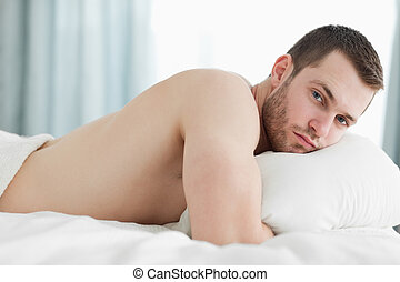 Gorgeous man lying on his belly in his bedroom