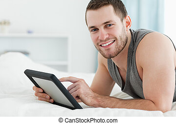 Smiling man using a tablet computer while lying on his belly