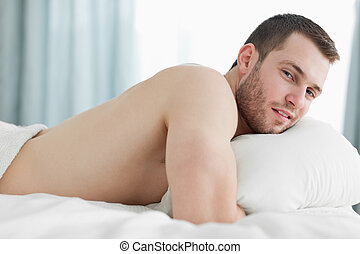 Serene man lying on his belly in his bedroom