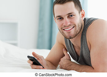Smiling man using his mobile phone in his bedroom