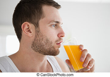 Close up of a healthy man drinking orange juice in his...