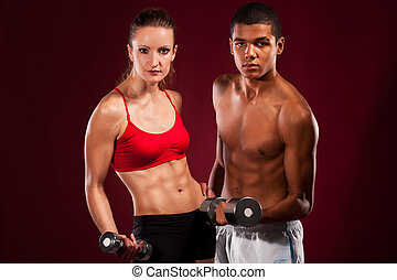 strong young couple working out with dumbbells