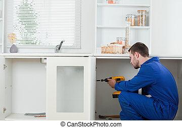 Handsome handyman fixing a door