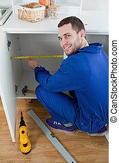Portrait of a smiling repair man measuring something