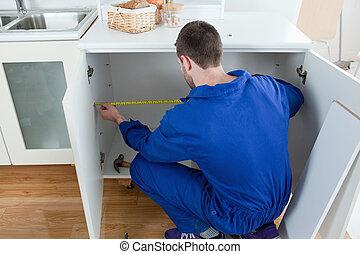 Repair man measuring something