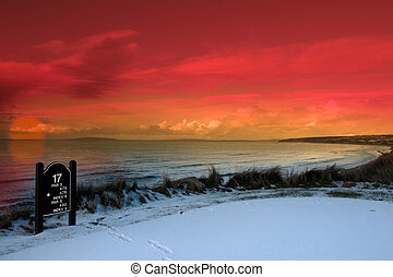 golf tee sign with winter orange sunset sky - a snow covered...