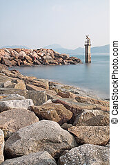 Lighthouse on a Rocky Breakwall: A small lighthouse warns of...