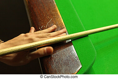 Young man concentrating while aiming at pool ball while...