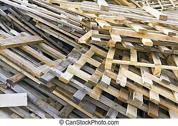 piled into a heap of wooden pallets - background of piled up...
