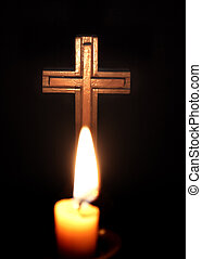 cross and candles over dark background