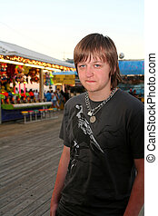 Sad Teen On Festive Boardwalk - Teenage boy with a sad,...
