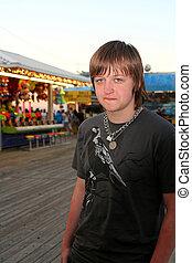 Sad Teen On Festive Boardwalk - Teenage boy with a sad,...