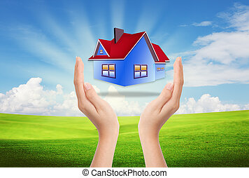 The House in the hands against the blue sky as a symbol of...