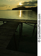 Sunset on a boat dock - A boat dock on tropical beach with...