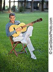 Man Playing Guitar Sitting in Lawn