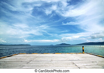 An empty boat dock on tropical beach with clean water and...