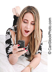 Happy and surprised girl looking on mobile phone
