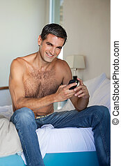 Shirtless Man Using Cell Phone - Portrait of shirtless man...