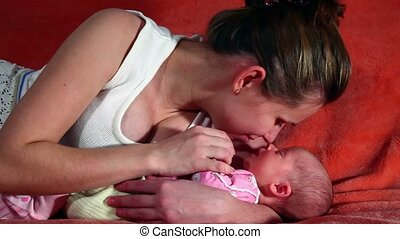 Baby sleeps on his mothers arms - Close-up of mother and...