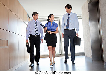 Businesspeople Walking In Office Corridor