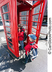 Boy talking in pay phone box - Boy talking in traditional...