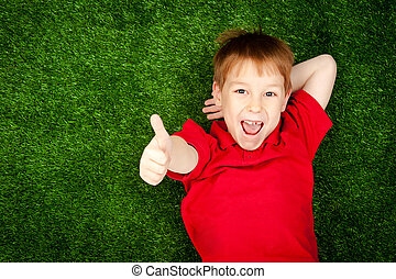 boy lying on a green lawn - cute little boy lying on a green...