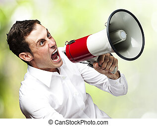 man with megaphone - portrait of young man screaming with...