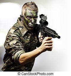 young soldier - portrait of young soldier aiming with rifle...