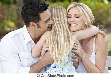 Girl Child Hugging Happy Parents In Park or Garden - A young...
