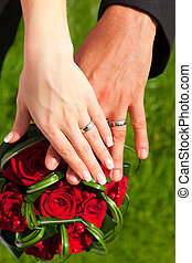 the hands with rings on wedding bouquet