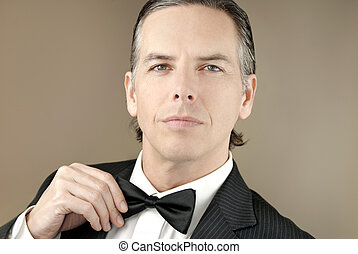 Confident Gentleman In Tux Adjusts BowTIe - Close-up of a...