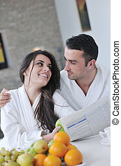 Happy couple reading the newspaper in the kitchen at...