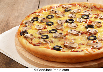 Mushroom pizza on the wooden board closeup