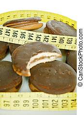 Chocolate cookies and measure tape  - loose weight concept