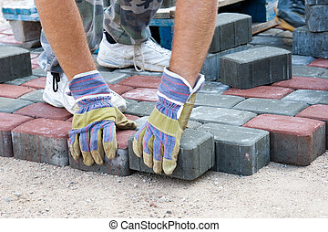 brick paver - a worker made a sidewalk from bricks