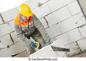 construction mason worker bricklayer sawing off a calcium...