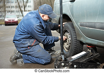 machanic repairman at tyre fitting with car jack - mechanic...