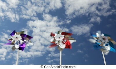 Pinwheels spinning in breeze against blue sky and clouds
