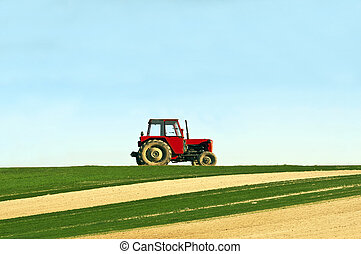 Tractor in a field - agricultural scene in summer