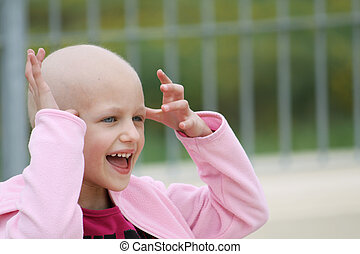 child with cancer - happy child who lost her hair due to...