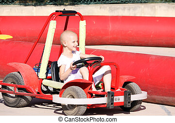 child on go kart - a caucasian child undergoing cancer...