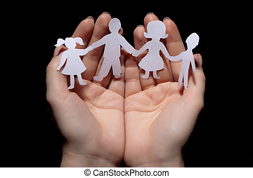 Paper chain family protected in cupped hands on black...
