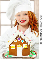 Adorable girl child in chef uniform holding a ginger bread,...