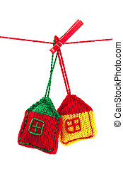 two knitted colorful houses on a red string isolated on...