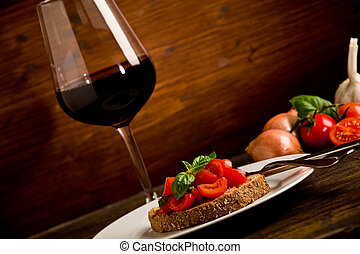 Bruschetta appetizer with red wine on wooden table - photo...