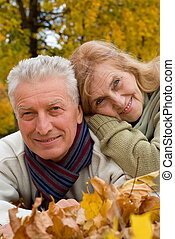 old couple on leaves - cute old couple lying on autumn...