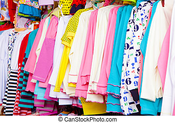a lot of clothes on a hanger - a lot of bright children's...